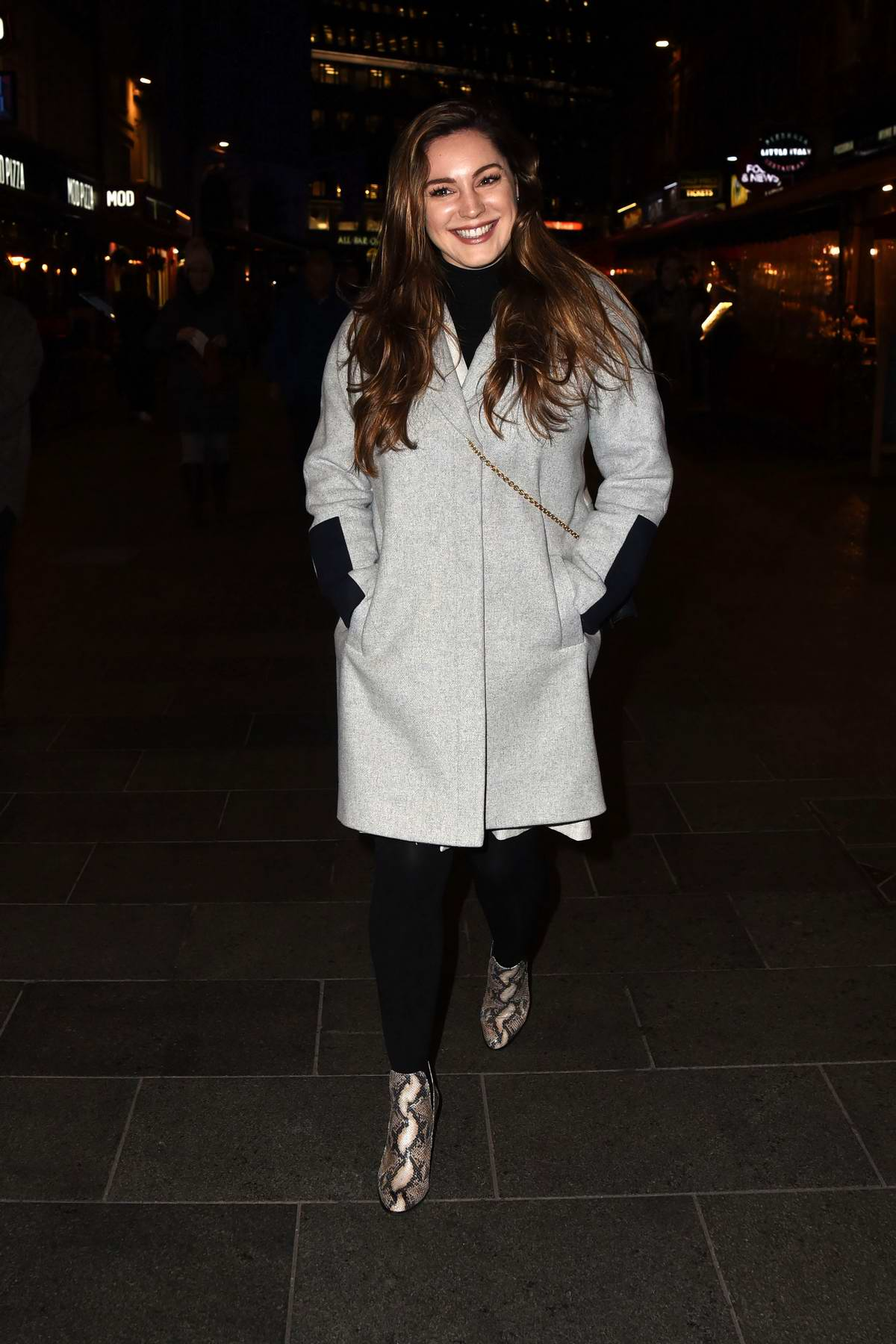 Kelly Brook is all smiles while out for stroll wearing a grey coat, black leggings and snakeskin boots in London, UK