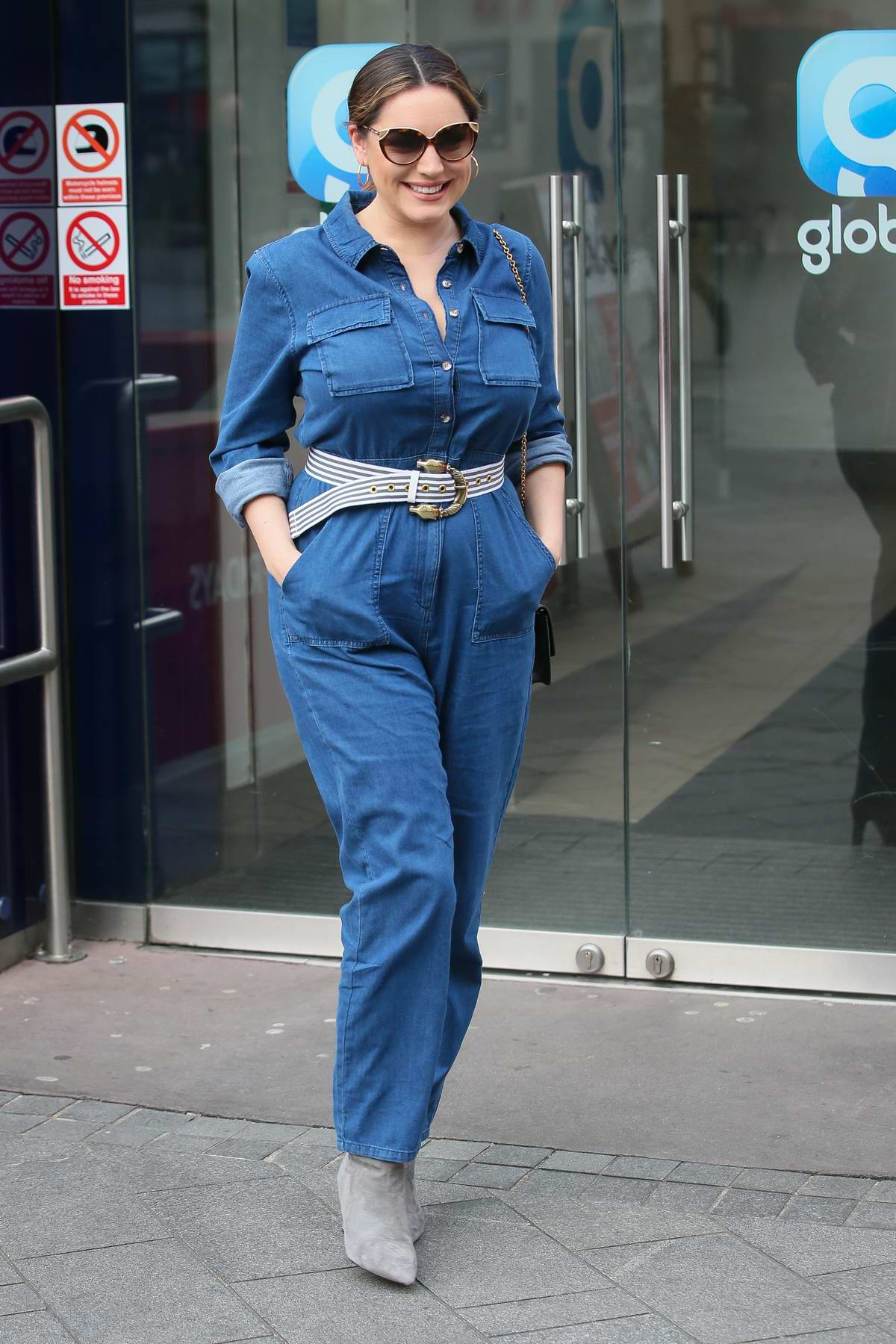 Kelly Brook looks lovely in a blue denim jumpsuit as she arrives at Global Radio studios in London, UK
