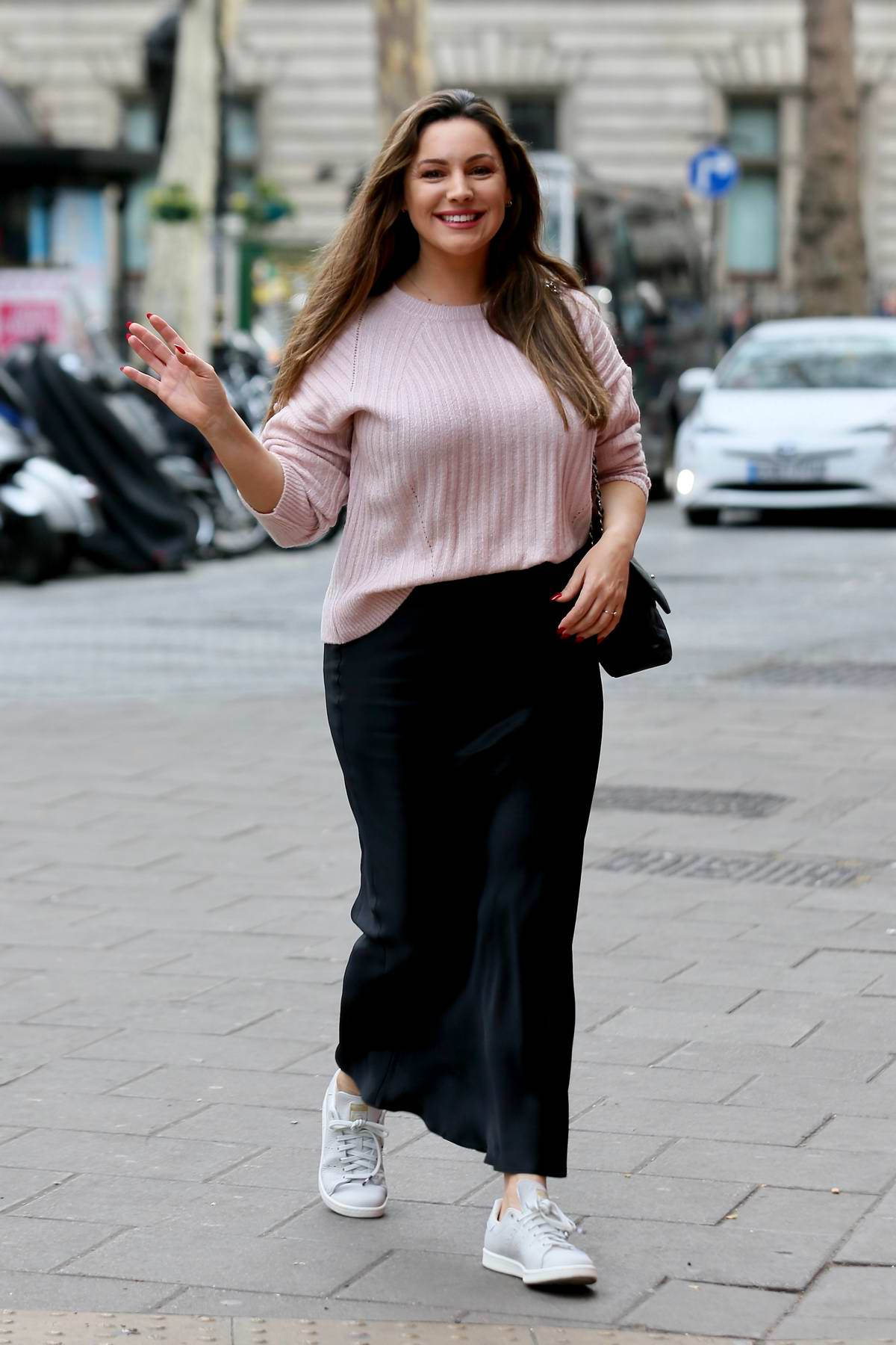 Kelly Brook looks lovely in a pink sweater and black long skirt as she arrives at Global Radio studios in London, UK