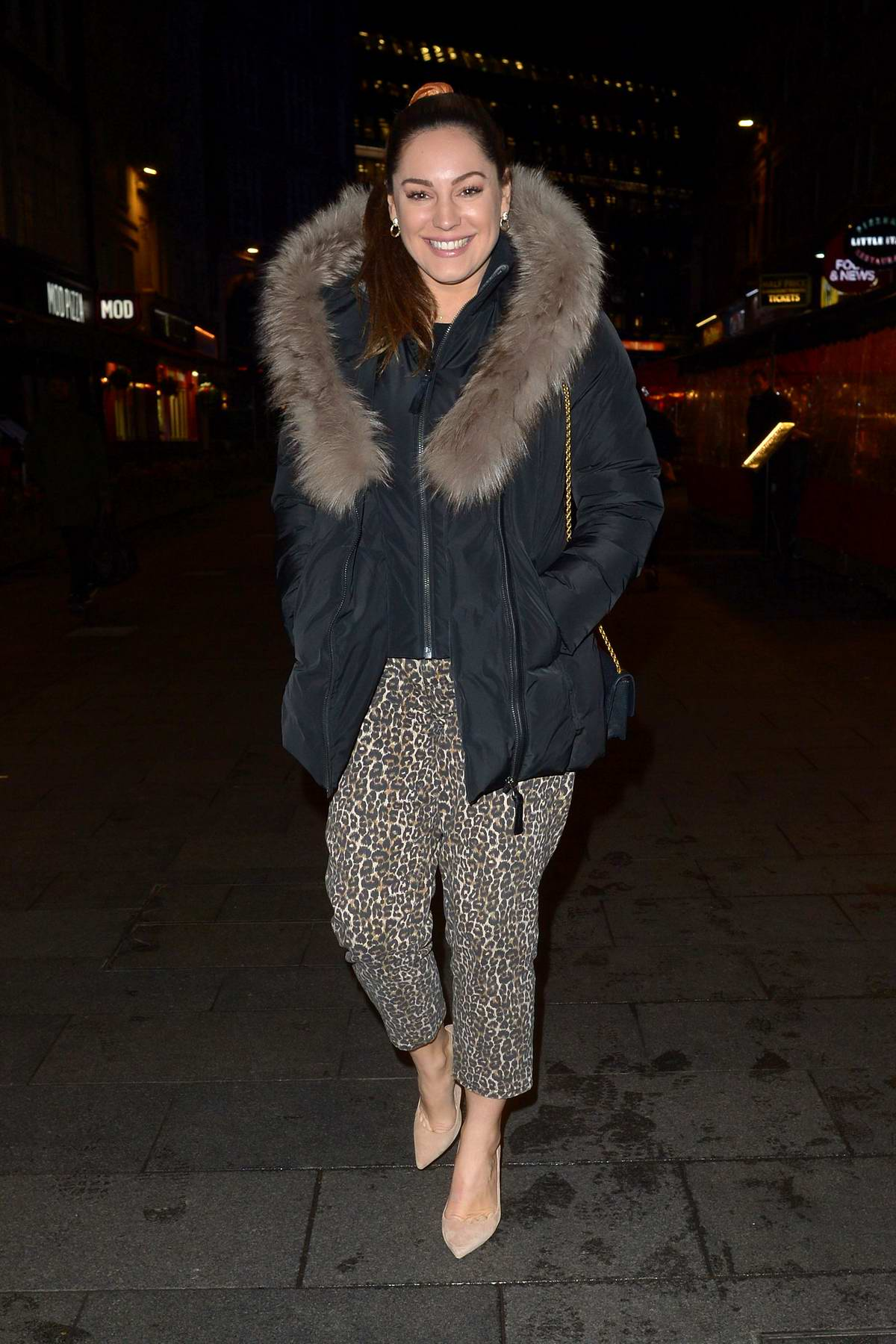 Kelly Brook wears a smile with a fur-lined jacket and leopard print pants as she leaves Global Radio in London, UK