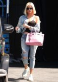 Khloe Kardashian dons denim jacket with ripped jeans and sneakers as she leaves a studio in Los Angeles