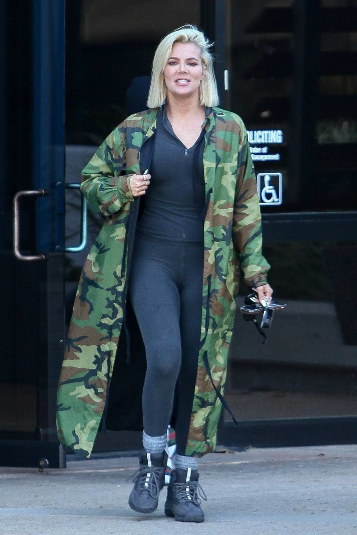 Khloe Kardashian wears a black jumpsuit with camo jacket as she leaves Kanye West's office In Calabasas, California