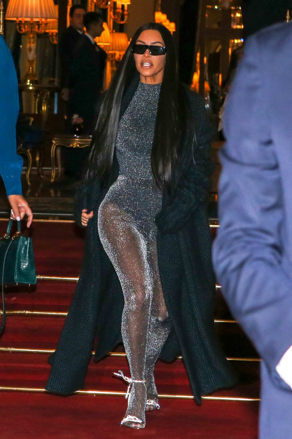 Kim Kardashian dons a long black coat with semi sheer tights as she leaves the Ritz Hotel in Paris, France