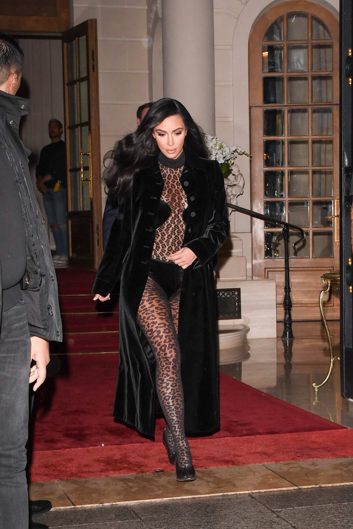 Kim Kardashian rocks an animal print bodysuit with a black long coat as she heads out of the Ritz Hotel in Paris, France