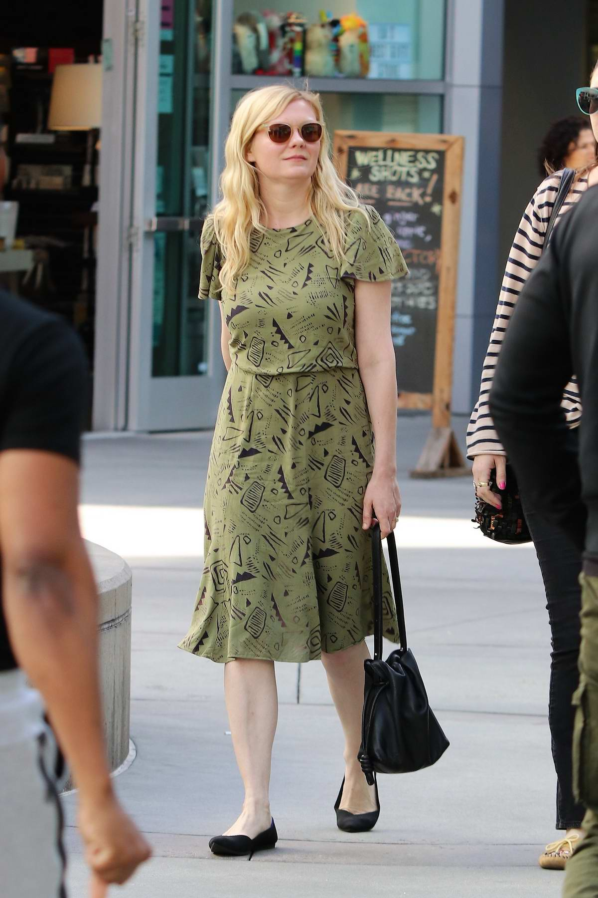 Kirsten Dunst looks casual in a green summer dress as she steps out to see a movie with a friend in Los Angeles