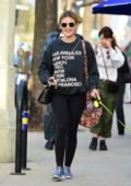 Lucy Hale rocks a Chanel purse with black sweatshirt, leggings and blue sneakers while walking her dog in Studio City, Los Angeles