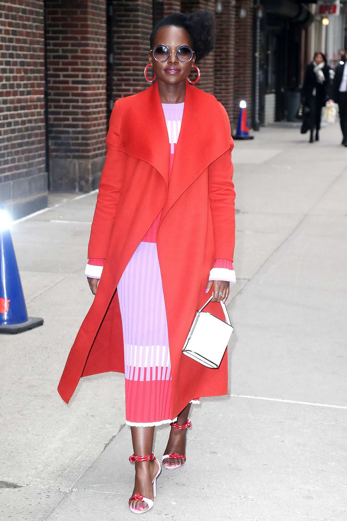 Lupita Nyong'o stands out in a bright red coat while visiting 'The Late Show with Stephen Colbert' in New York City