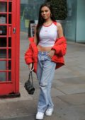 Madison Beer shows off her street style in a white Fendi tank top with a red puffy jacket and ripped jeans while out in London, UK