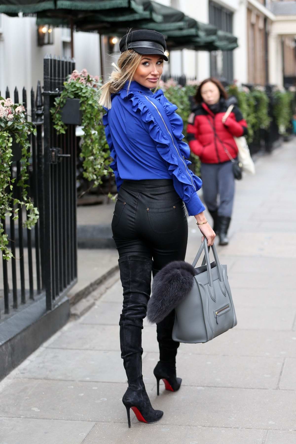 Megan McKenna seen wearing a blue silk shirt and black leather pants while out for a business meeting in Soho, London, UK