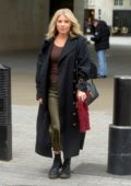 Mollie King wears a black long coat, brown sweater and green skirt as she leaves the BBC Radio 1 studios in London, UK