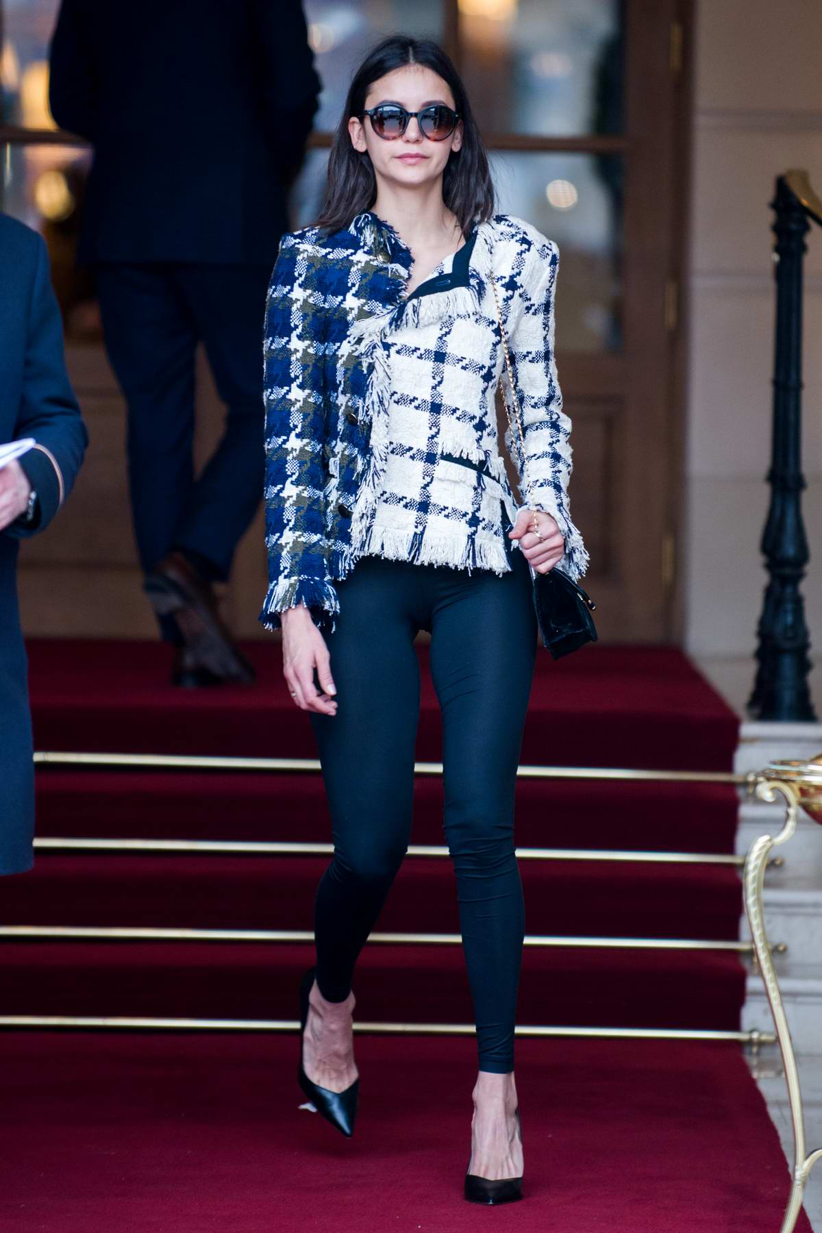 Nina Dobrev dons a stylish dark blue and white checkered jacket and black leggings as she leaves the Ritz Hotel in Paris, France