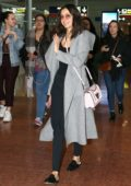 Nina Dobrev looks casual yet trendy in a grey long coat paired with a black outfit and pink Louis Vuitton purse as she arrives CDG Airport in Paris, France