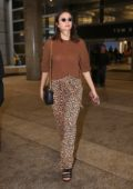 Nina Dobrev seen wearing a brown sweater and animal print pants as she touches down at LAX in Los Angeles