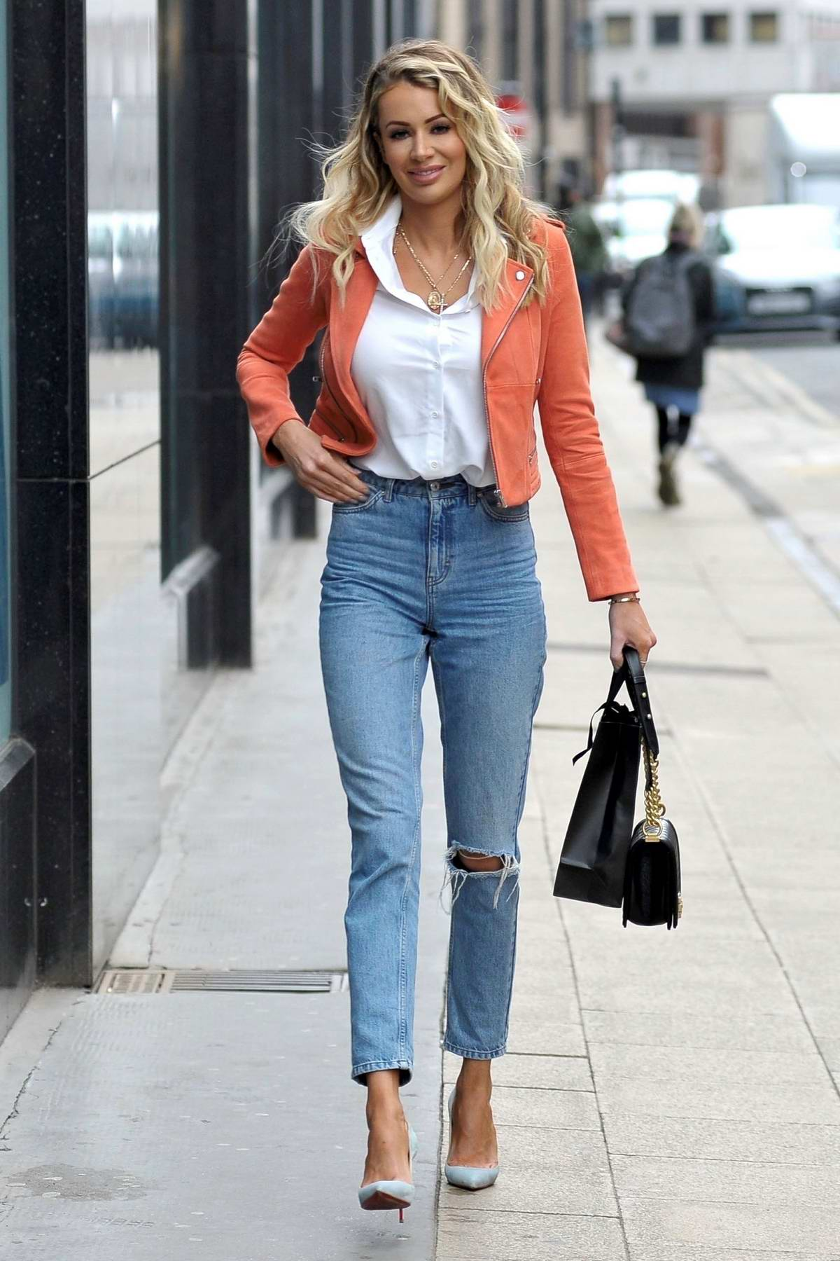Olivia Attwood wears an orange jacket with a white shirt and jeans while out shopping in Manchester, UK