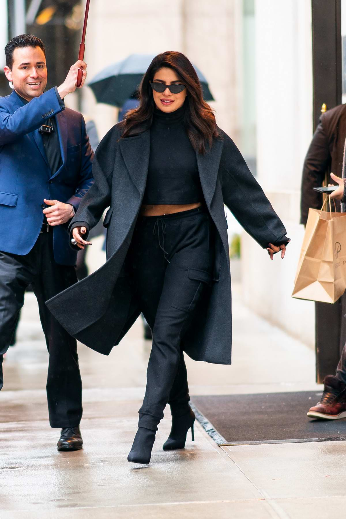 Priyanka Chopra rocks a dark grey wool coat, cropped black turtleneck, matching sweats, and black boot while out in New York City