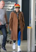 Rita Ora wore a colorful beanie and a long brown coat with black and blue leggings as she touched down at Melbourne Airport, Australia