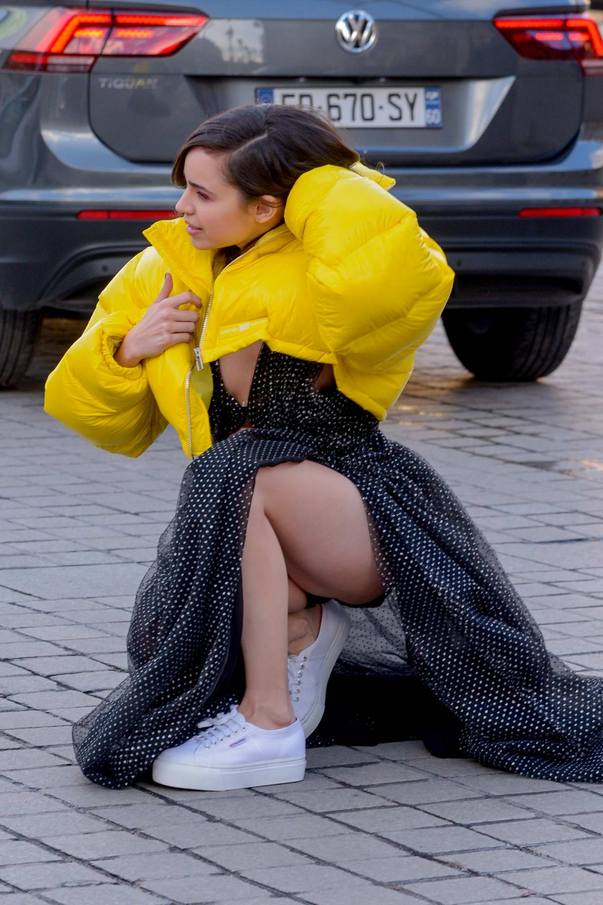 Sofia Carson pose for photos in a bright yellow puffer jacket with a black dress and white sneakers while out in Paris, France