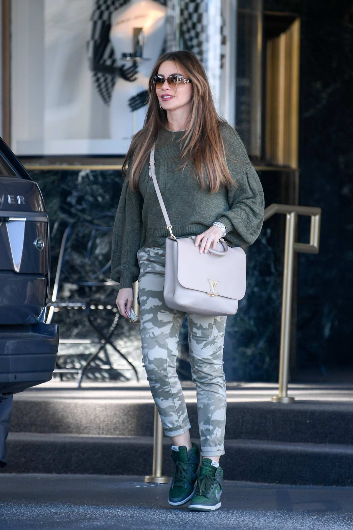 Sofia Vergara looks stylish in a green sweater, camo pants and Nike trainers while out shopping at Saks Fifth Avenue in Los Angeles