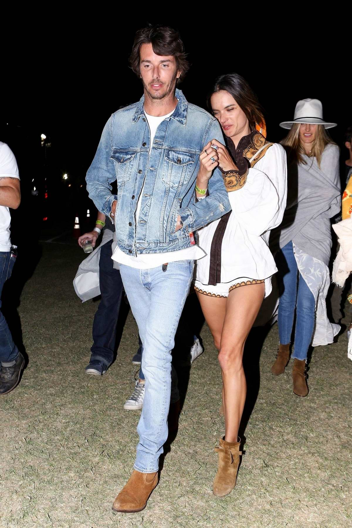 Alessandra Ambrosio holds on tight to Nicolo Oddi while out during Coachella in Indio, California