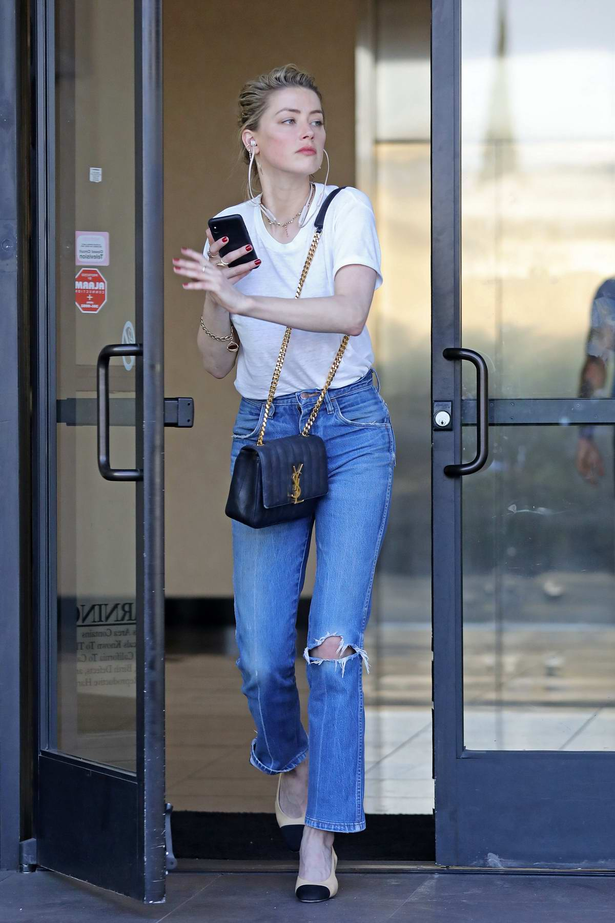 Amber Heard keeps it casual with a white tee and blue jeans while visiting a lawyer's office in Los Angeles