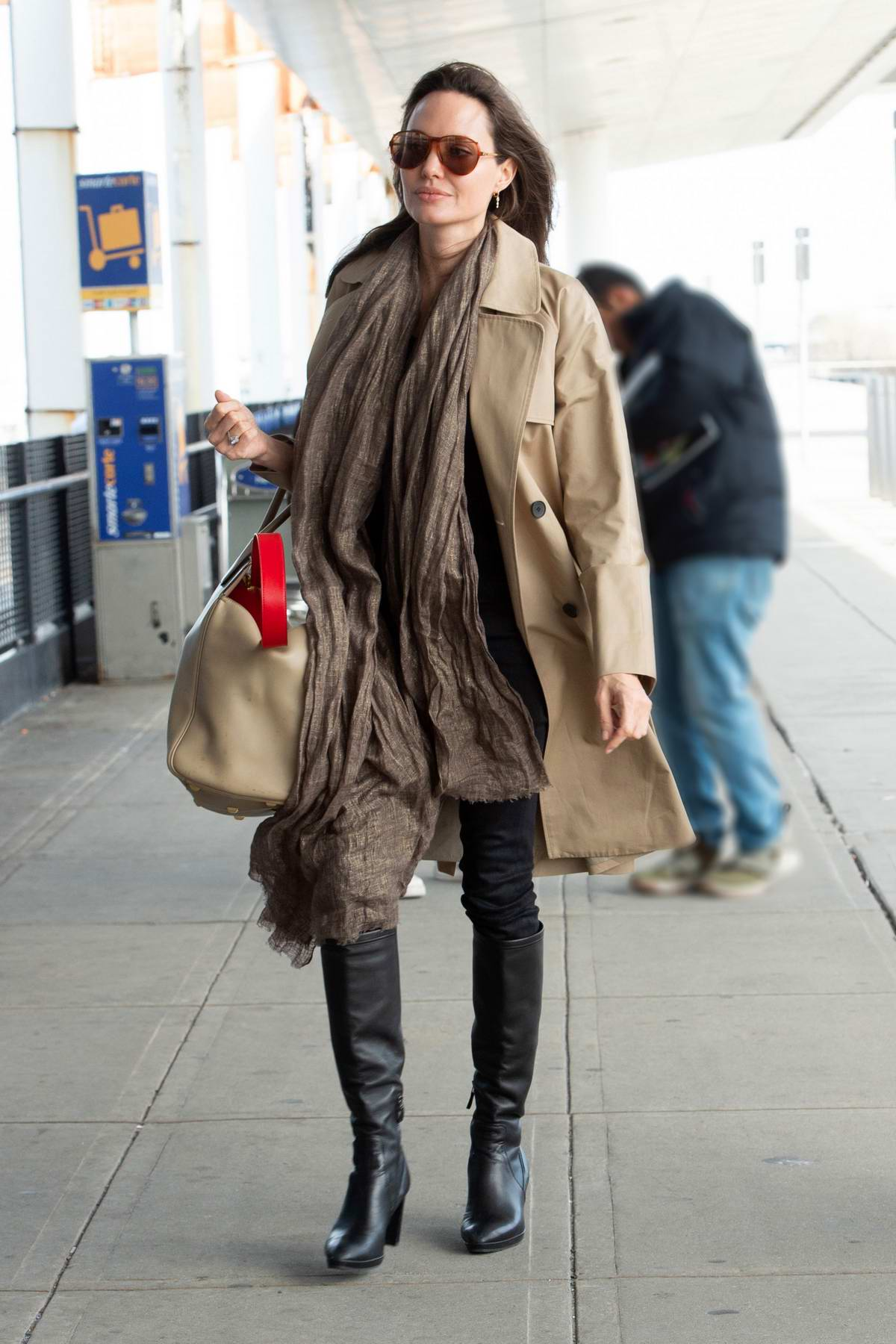 Angelina Jolie waves for the camera as she arrives at JFK Airport in New York City
