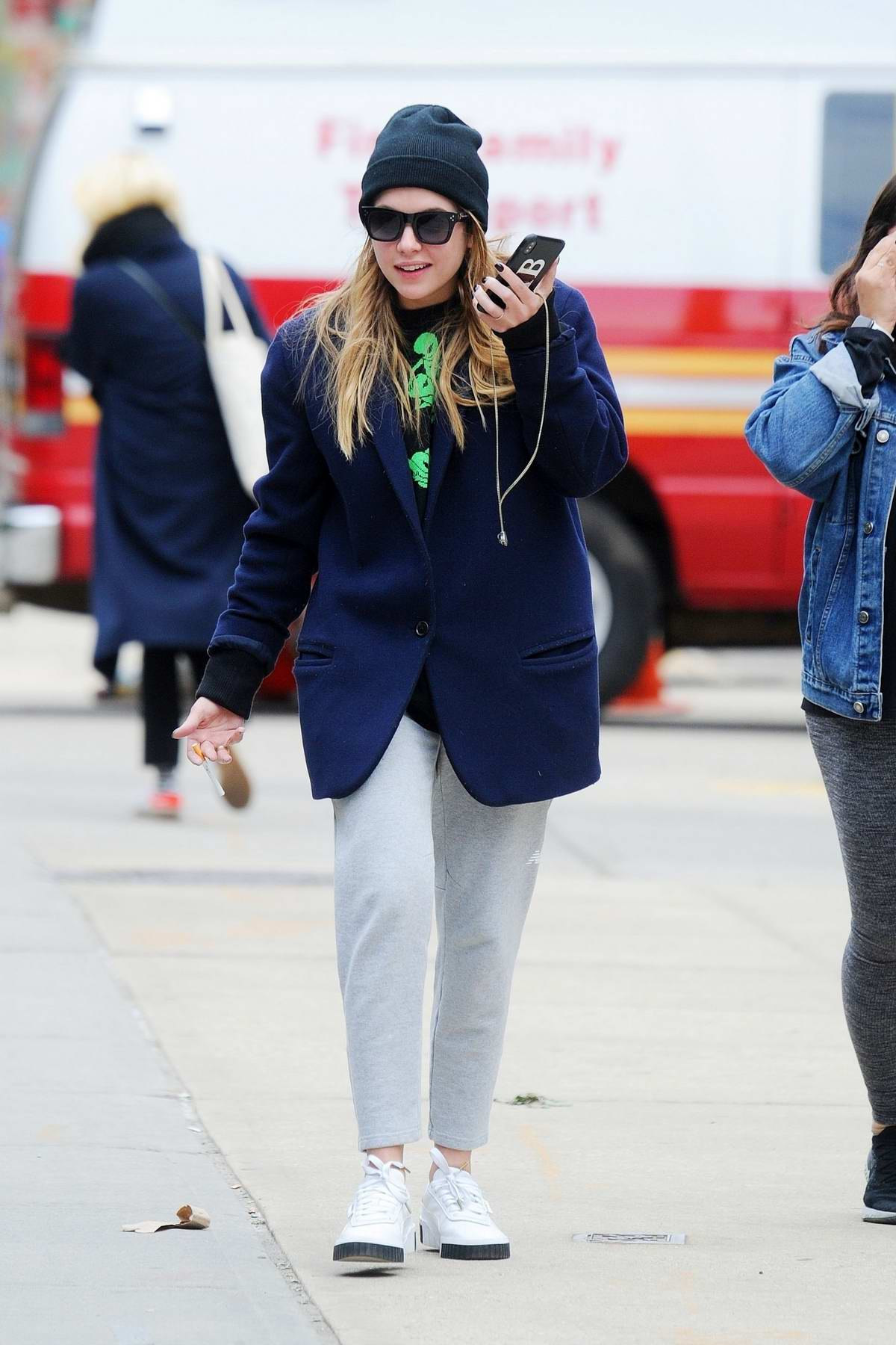 Ashley Benson grabs a smoke while out for a stroll with a friend in New York City