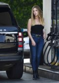Ashley Benson spotted in a black top and blue skinny jeans as she fills up her Range Rover at a gas station in Hollywood, California