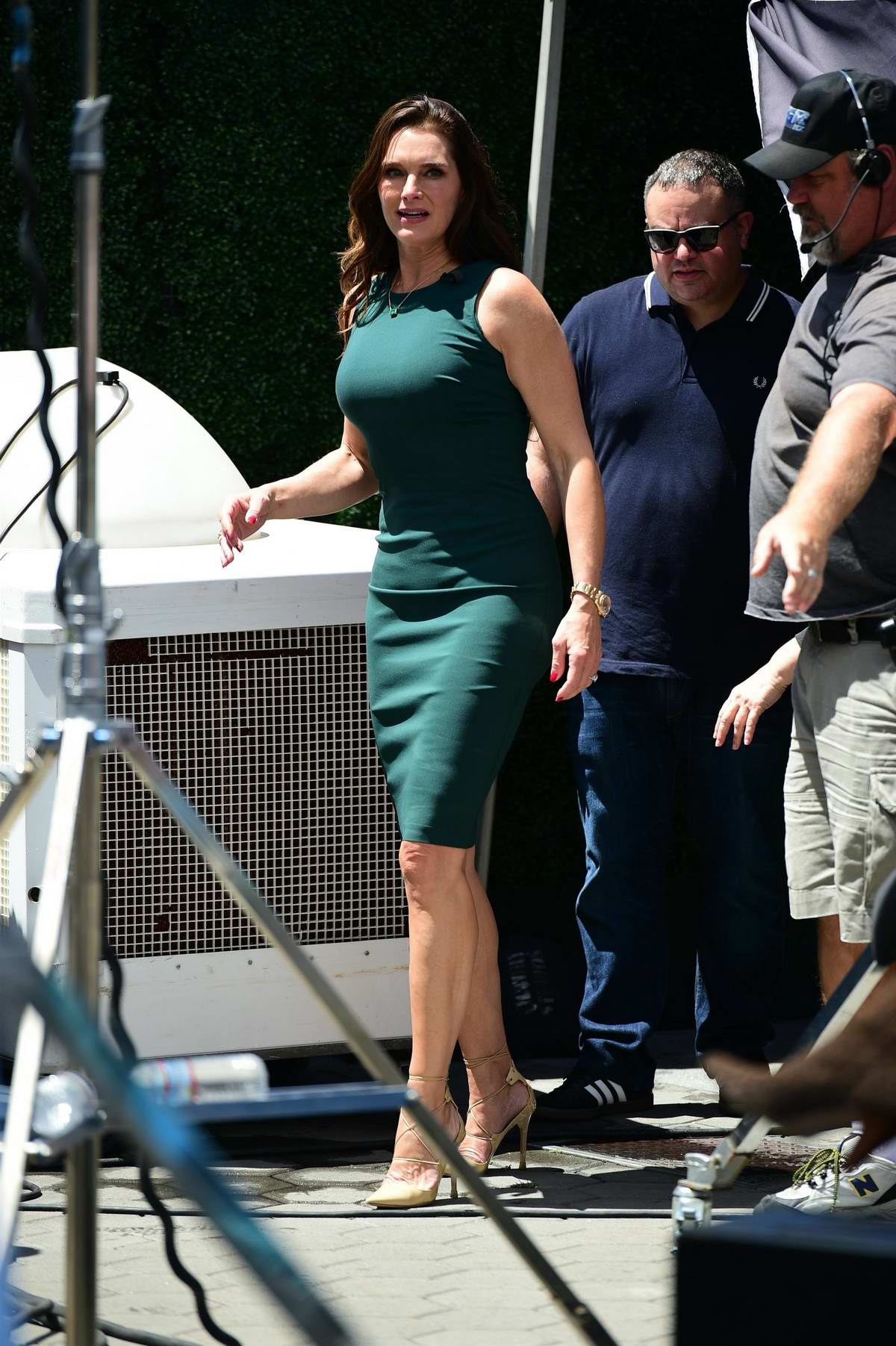 Brooke Shields wears a form-fitting green dress for her appearance on 'Extra' TV Show at Universal Studios in Los Angeles