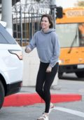 Charlize Theron keeps things casual with grey hoodie, black leggings and sandals as she steps out in Los Angeles