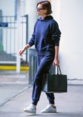 Charlize Theron looks cool in blue sweatsuit with dark shades and white sneakers as she arrives at JFK Airport in New York City