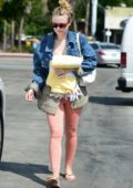 Dakota Fanning wears an denim and plaid jacket over a pink bodysuit as she leaves the gym in Los Angeles