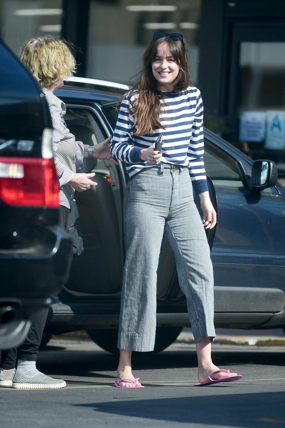 Dakota Johnson greets a friend as she leaves a pedicure before heading to Trader Joe's in Los Angeles