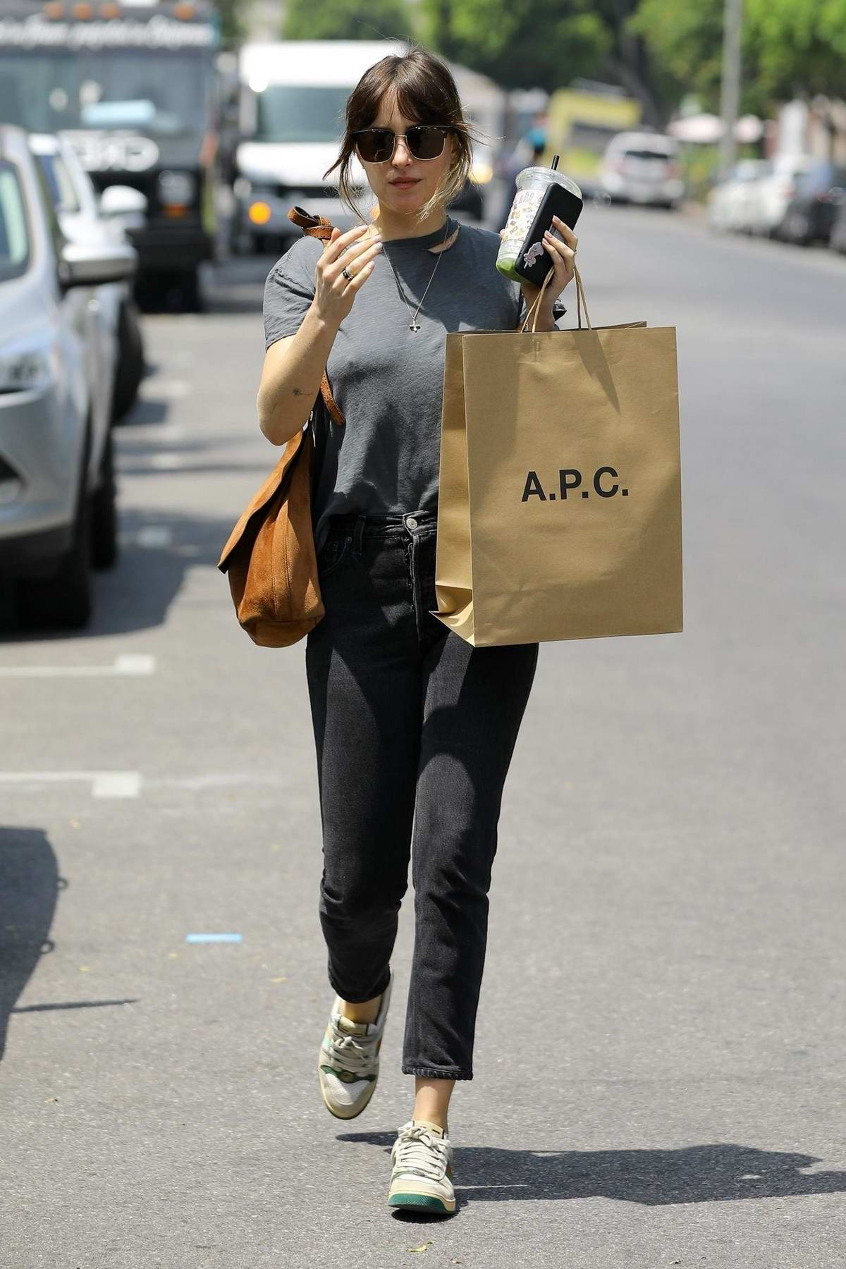 Dakota Johnson wears grey top, black jeans and Gucci sneakers during a shopping trip to A.P.C in Los Angeles