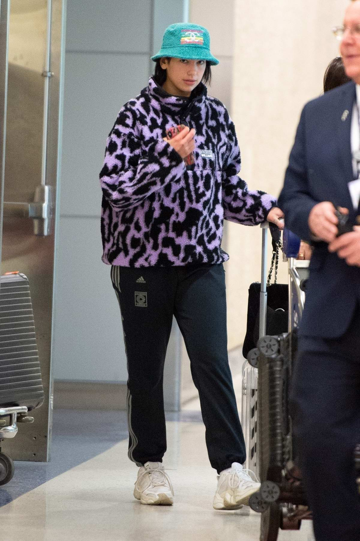 Dua Lipa wears an animal print purple fleece with Chanel hat as she touches down at JFK Airport in New York City