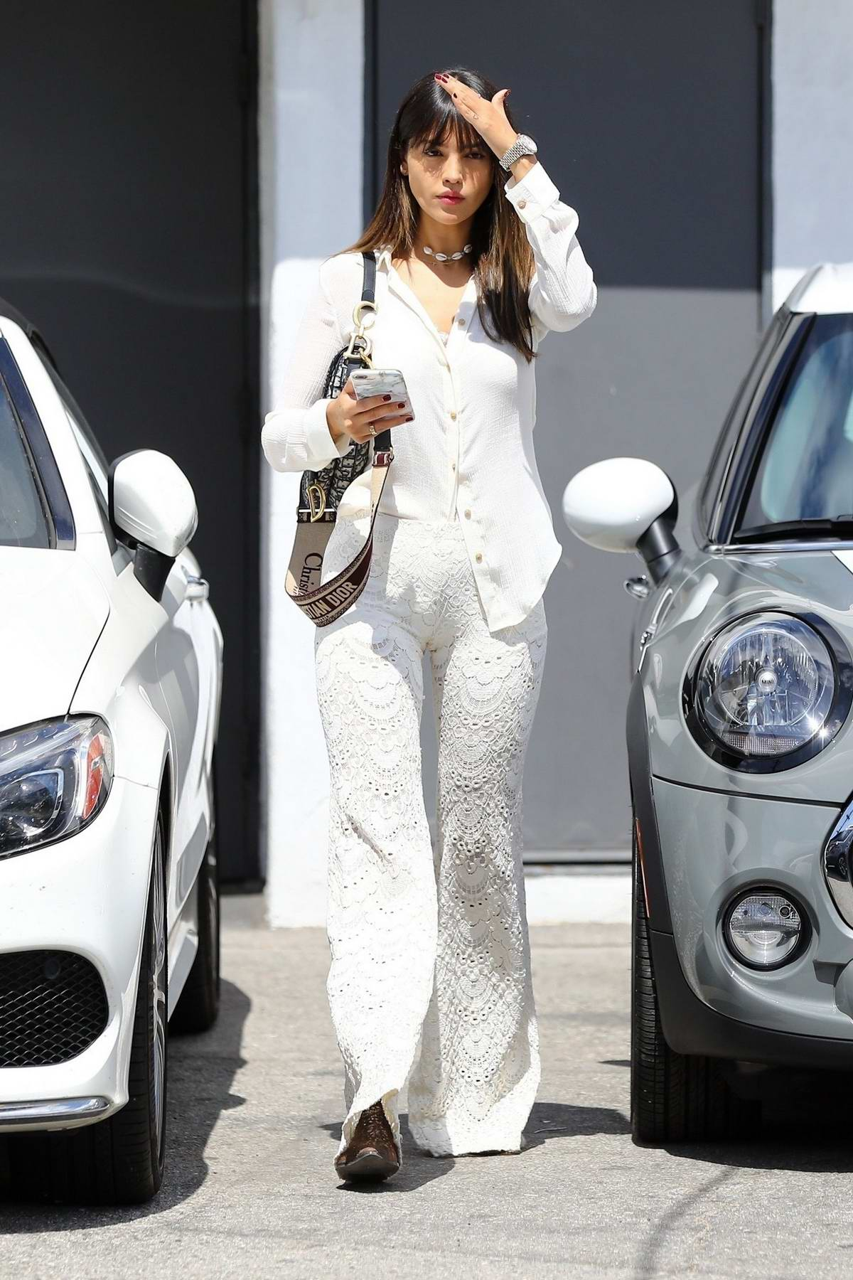 Eiza Gonzalez dons a white shirt with matching crochet trousers and a Christian Dior tote bag while leaving a hair salon in Los Angeles