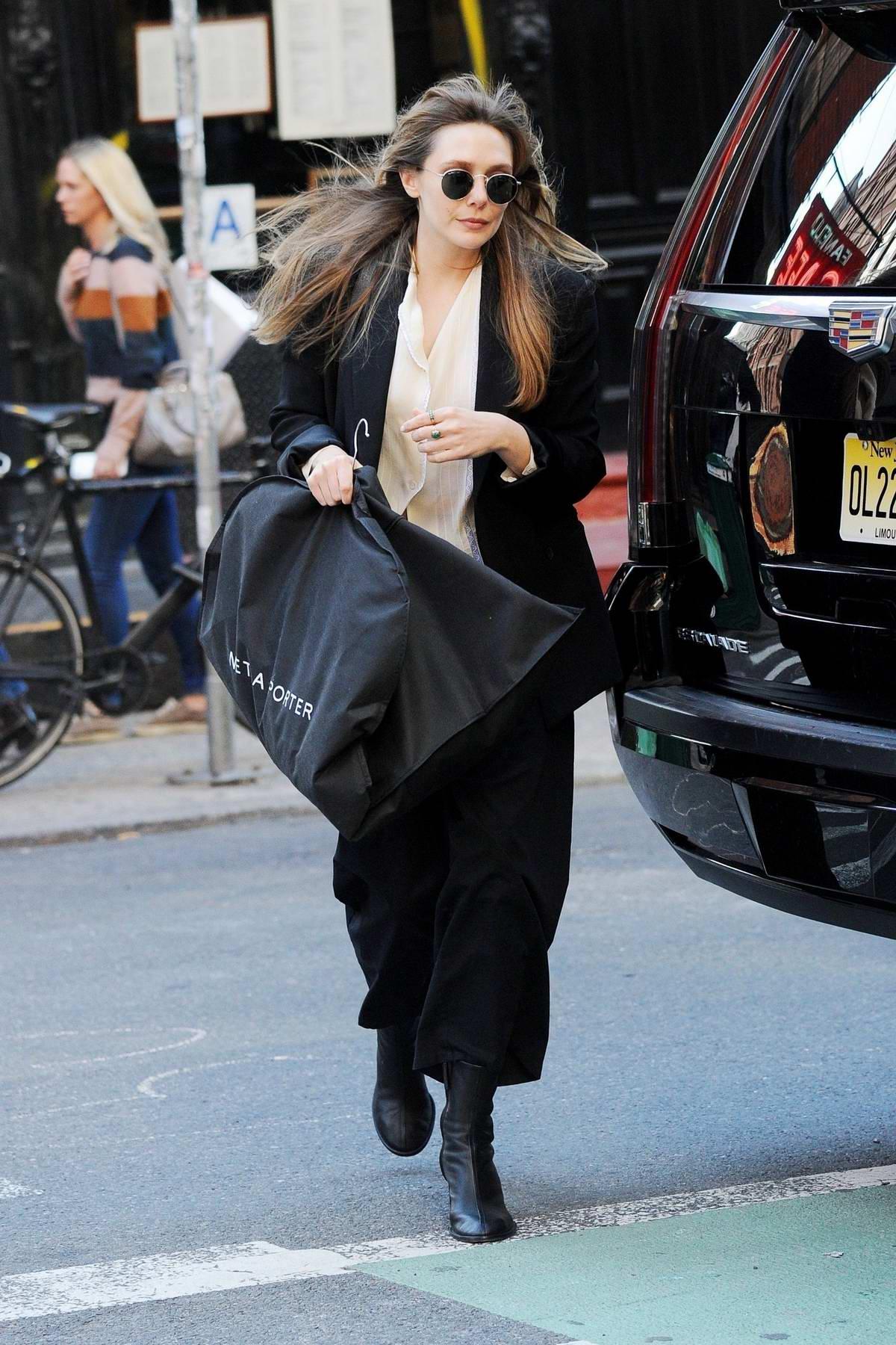 Elizabeth Olsen steps out with a garment bag in New York City