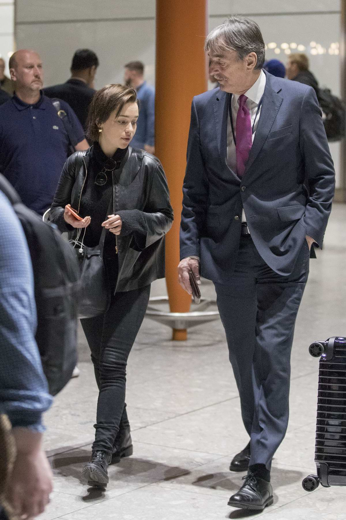 Emilia Clarke sports an all black look as she touches down at Heathrow Airport in London, UK