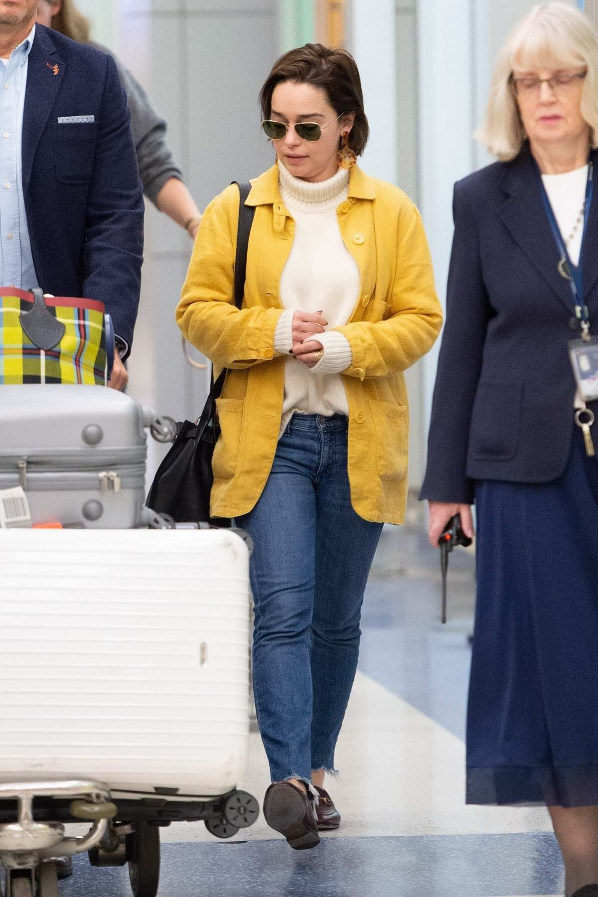 Emilia Clarke stand out in a yellow coat as she arrives at JFK airport in New York City