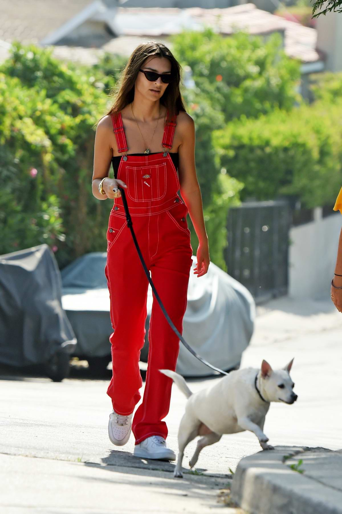 Emily Ratajkowski rocks red overalls while out for a stroll with her dog in Los Angeles