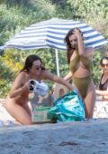 Emily Ratajkowski slips into a green swimsuit as she spends the afternoon with friends at the beach in Malibu, California