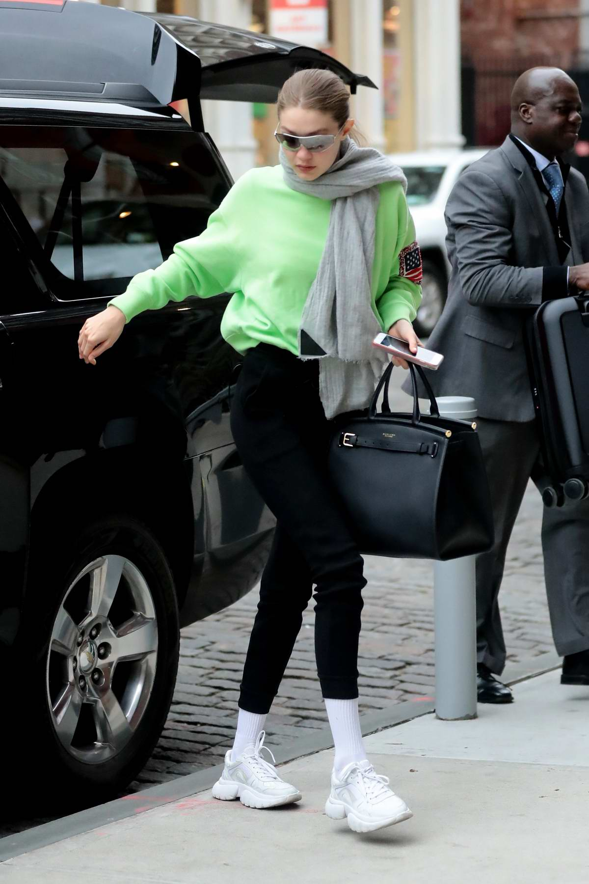 Gigi Hadid keeps it trendy in a lime green sweatshirt as she arrives at her apartment in Manhattan, New York City