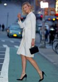 Karlie Kloss looks elegant in a white wrap dress with black heels as she steps out in Manhattan, New York City