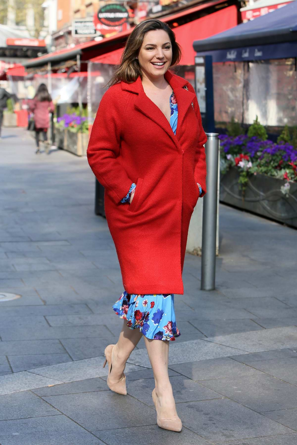 Kelly Brook is all smiles as she leaves Global Radio studios in a red coat over blue floral dress in London, UK