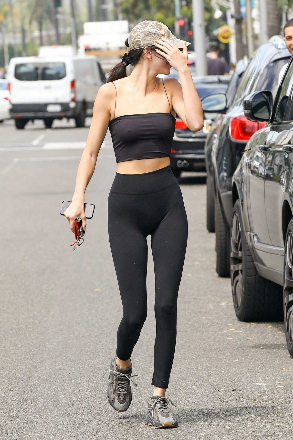 Kendall Jenner shows off her slender figure in a black crop top with matching leggings during a lunch outing in Beverly Hills, Los Angeles