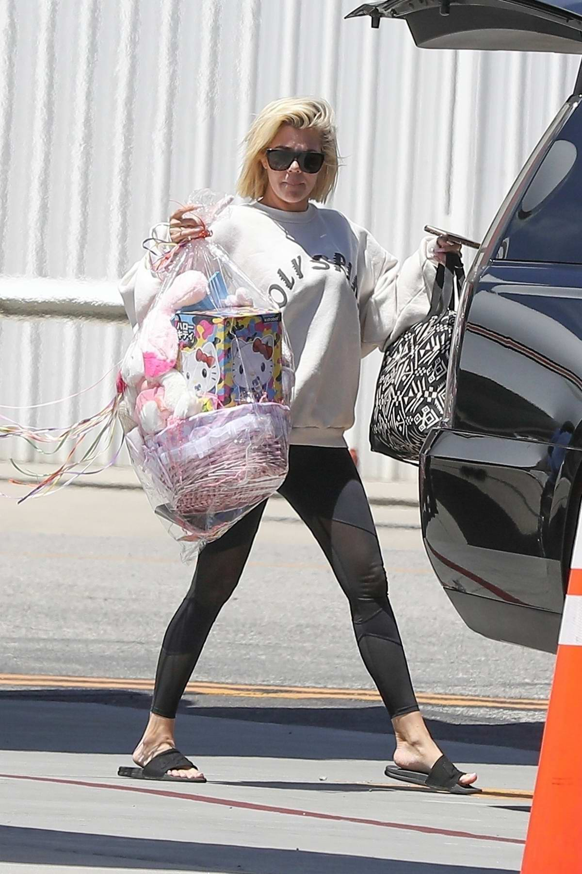 Khloe Kardashian arrives back with her baby from Palm Springs on a private jet at Van Nuys airport, California