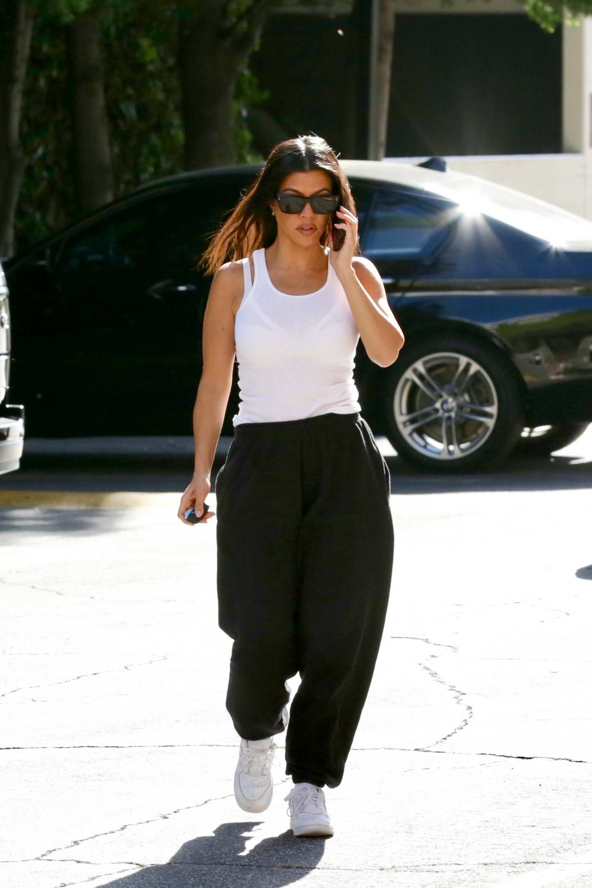 Kourtney Kardashian keeps it casual in a white tank top and black sweats while out in Calabasas, Los Angeles