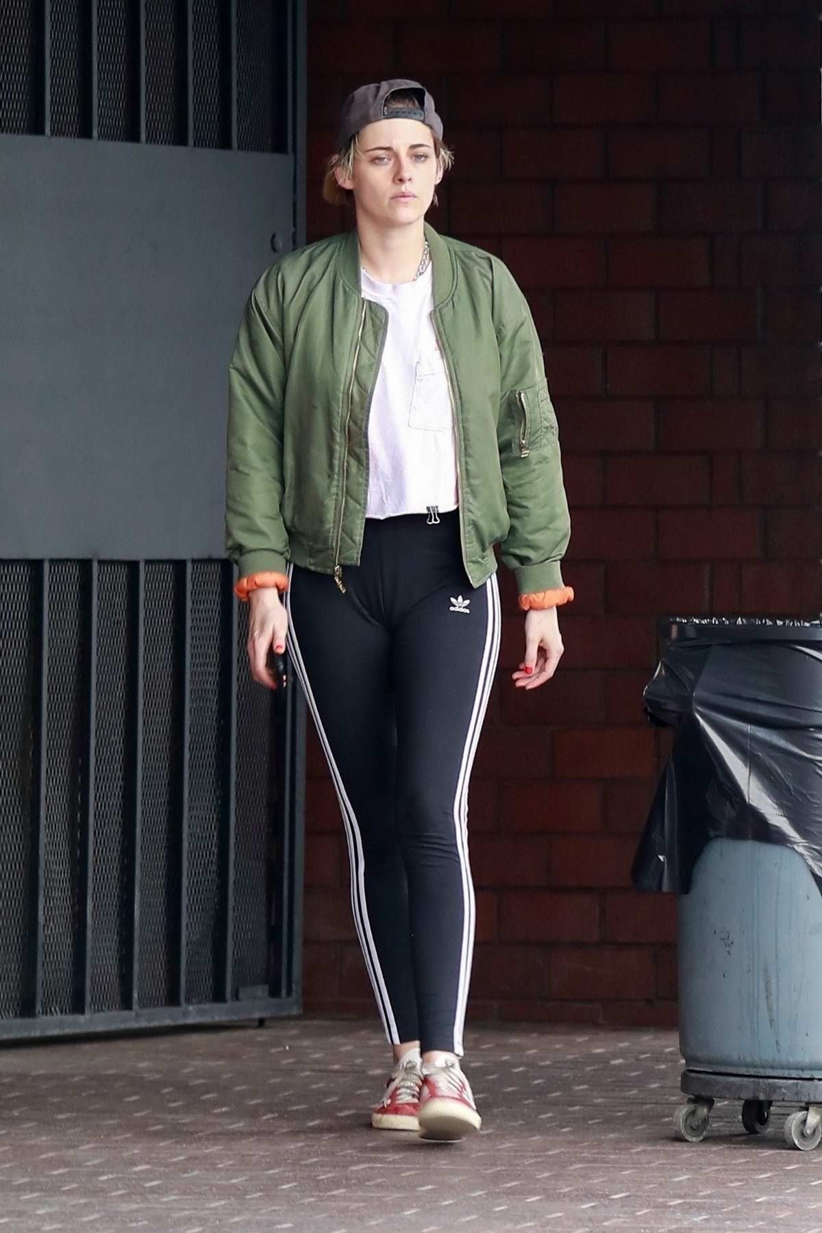 Kristen Stewart wears a green jacket and black Adidas leggings while visiting a Nail Salon in Hollywood, California