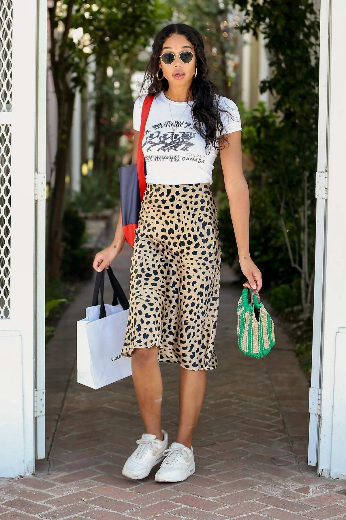 Laura Harrier steps out in a white top and leopard print skirt during a shopping outing in Los Angeles