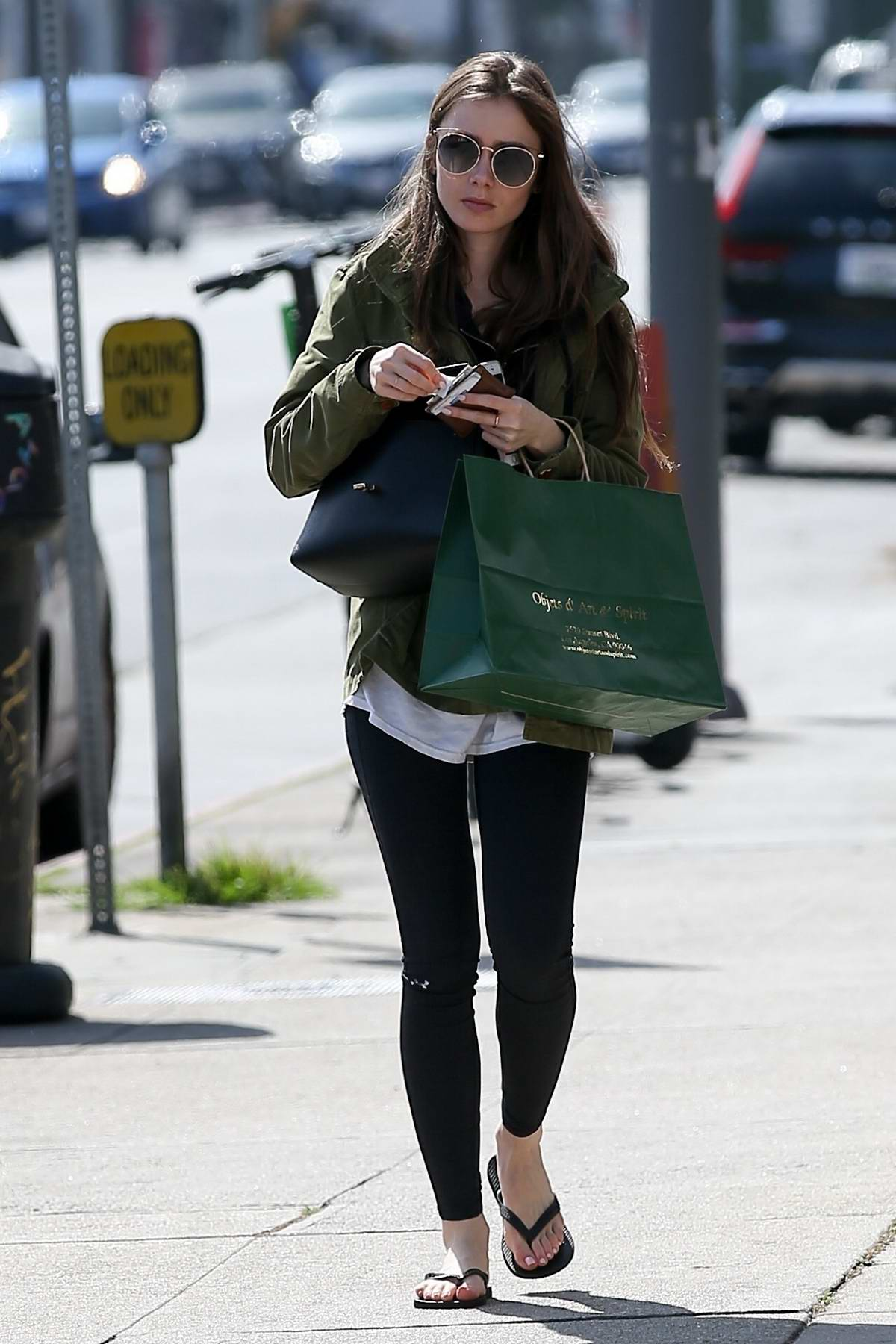 Lily Collins steps out in flip flops and military green jacket to do some shopping in Hollywood, California