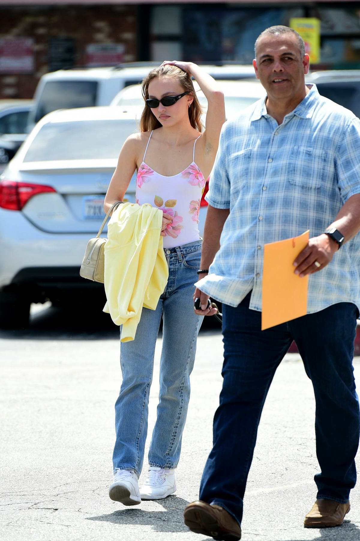 Lily-Rose Depp steps out in a floral tank top, jeans and Reebok sneakers as she run errands with her driver in Los Angeles